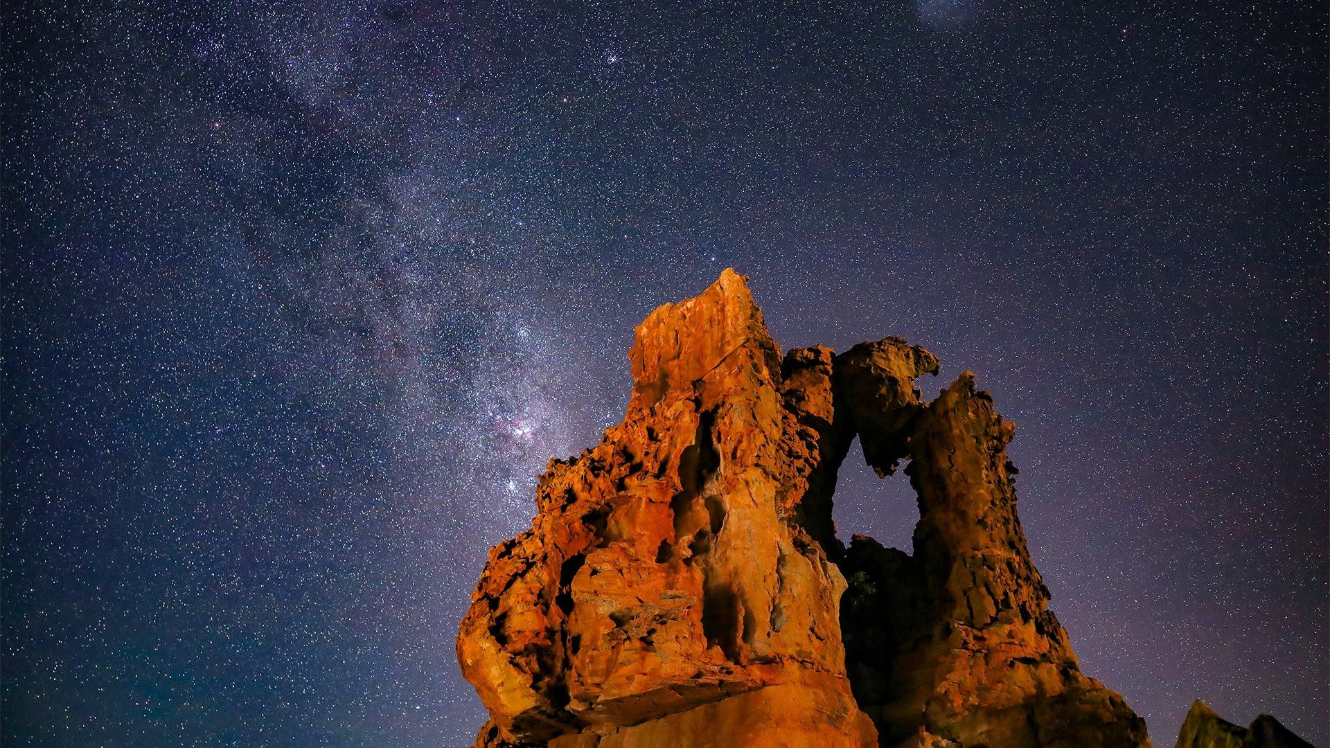 A rock formation standing stark against a sky filled with stars.
